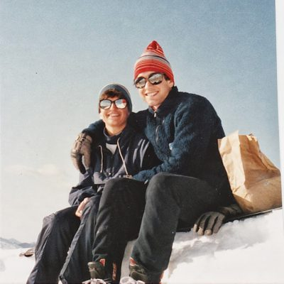 Ian Kraabel and a friend sit on a snowbank wearing sunglasses and stocking caps