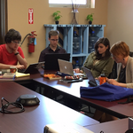 Students Elliot Schwartz '19, James Smith '19, and Jordan Kobbervig '19 at the Dakotah Language Institute. Three students and one professor sit working at a table.