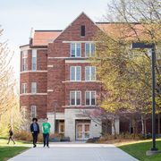 Two students walk past a dorm on the east side of the Carleton campus