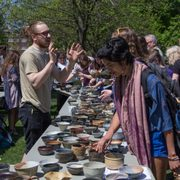 students examine pottery bowls on an outside table