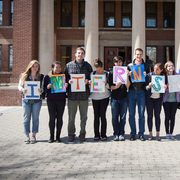 "A group of students in front of Sayles holding letters that spell ""internships"""