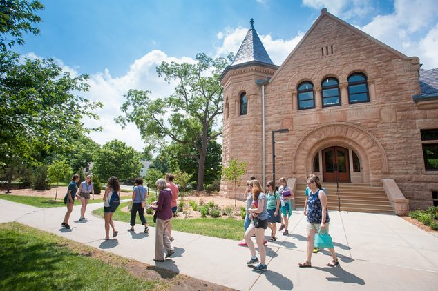 A student-led tour group leaves Admissions, most people in short sleeves