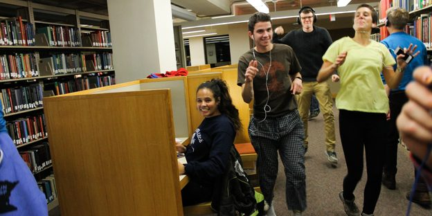 Students wearing earbuds dance through the library while another studies