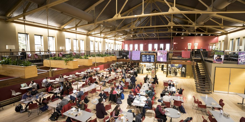 A crowd of people gather at tables for lunch in the large, vaulted space of Sayles-Hill Campus Center