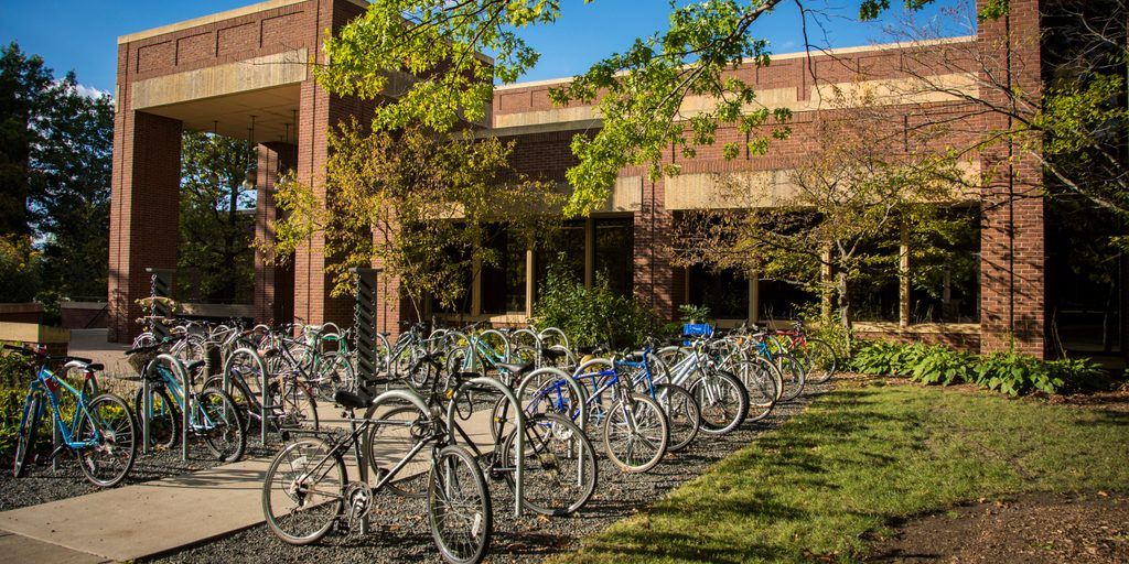 Many bikes line up at the bike racks by the main entrance to Gould Library