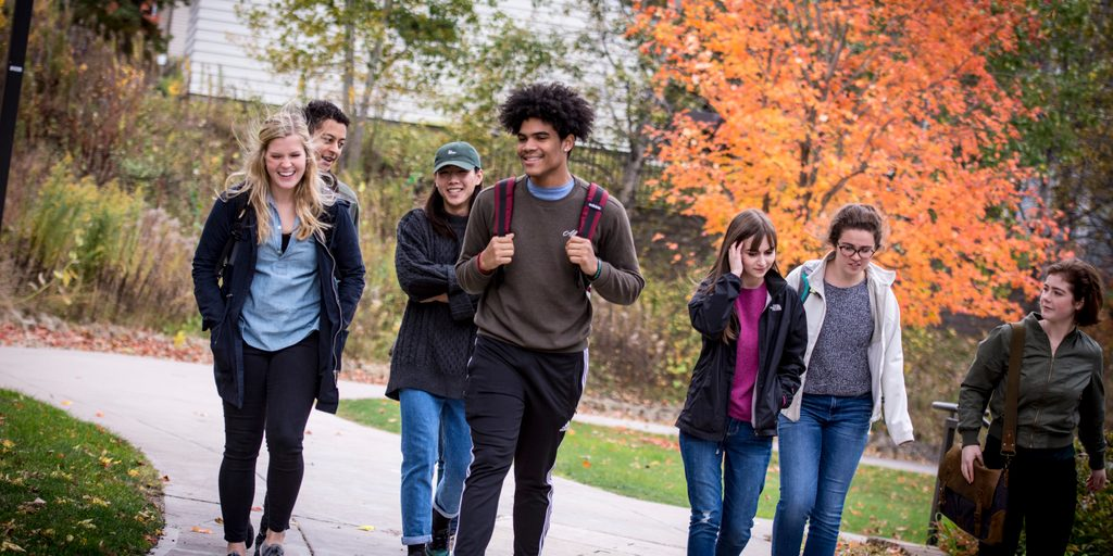 A group of students walks towards the camera, smiling and carrying backpacks