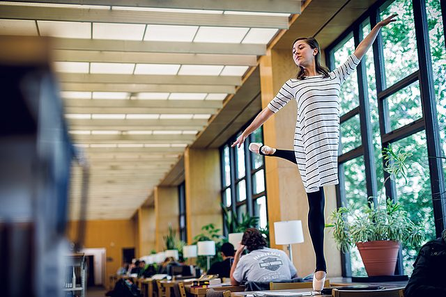 Carolyn Friedhoff stands en pointe on a desk between the library windows and stacks