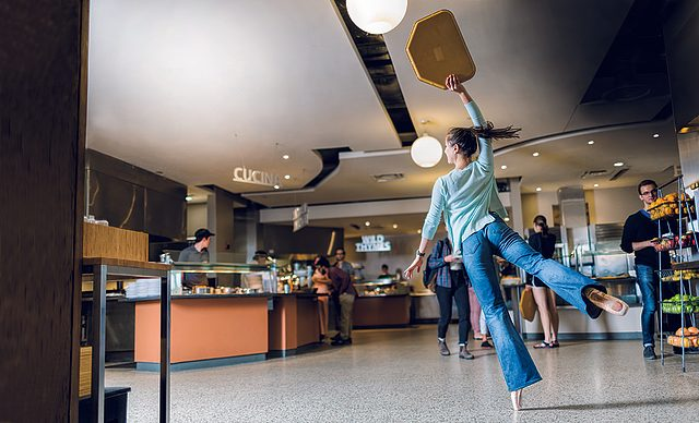 A student holding a tray dances en pointe in East Dining Hall