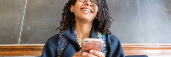 A student smiles broadly while playing on her phone