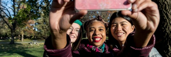 Three students smile as they take a selfie