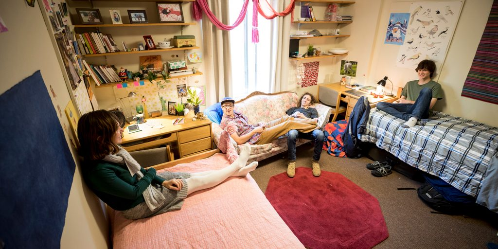 Four students relax in a dorm room