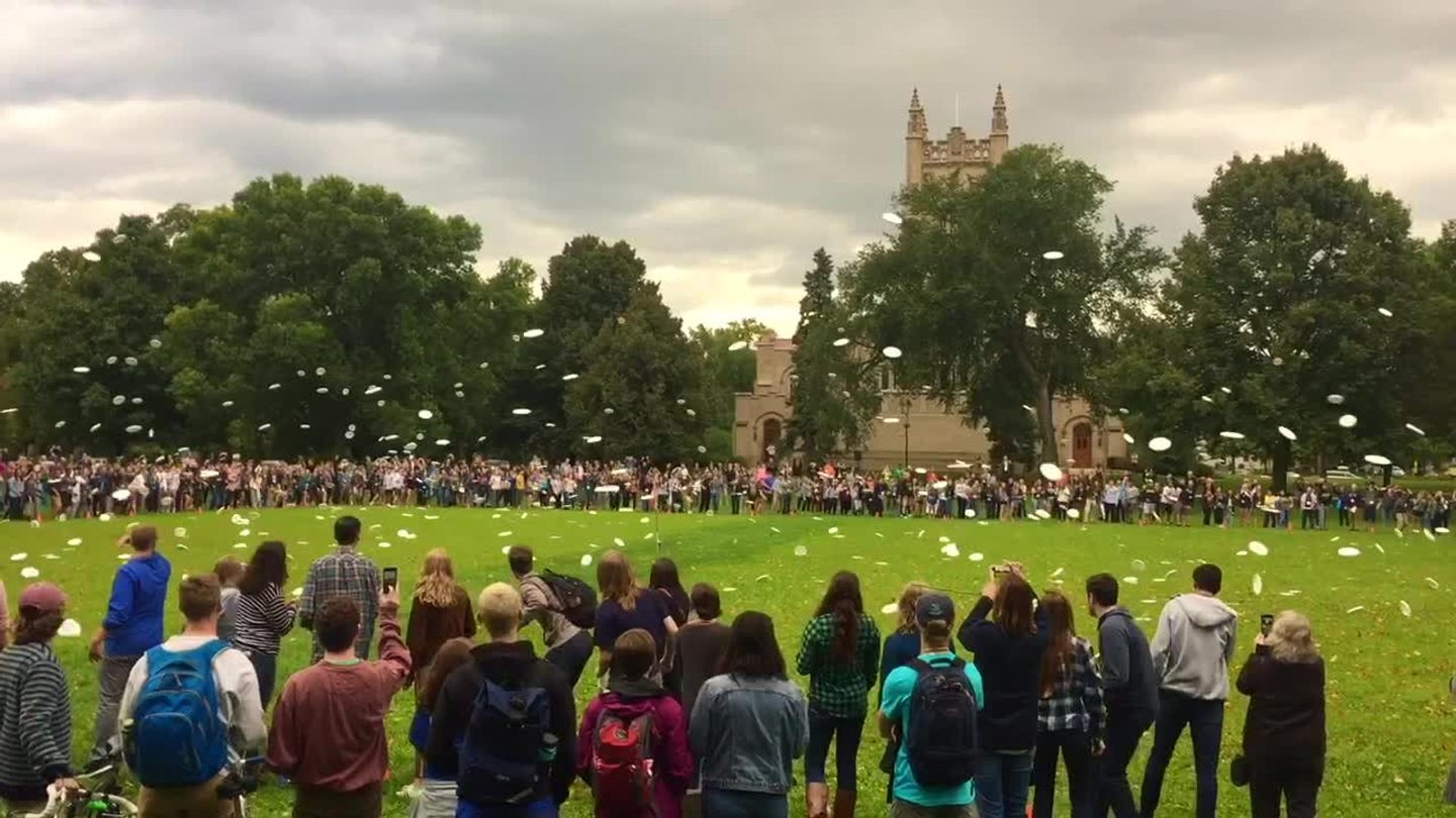 Video: A circle of several hundred students throw Frisbees on the Bald Spot