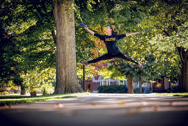 A student catches a frisbee while leaping across a campus path