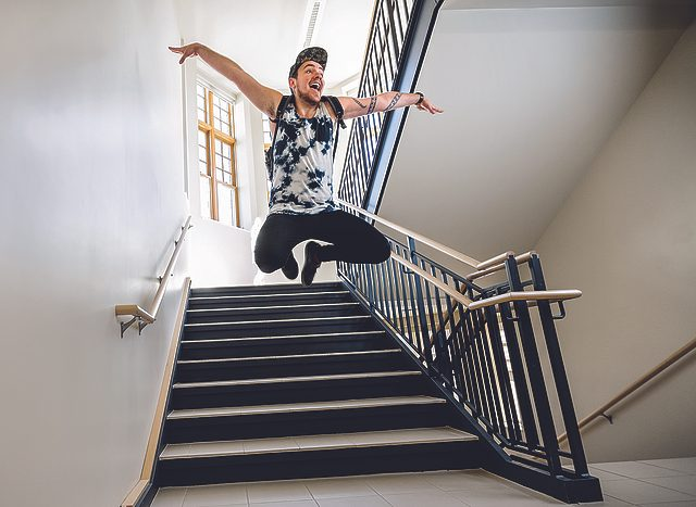 Mike Bahn in midair, arms extended, as he leaps in a dorm stairwell