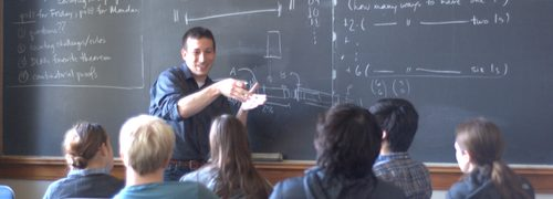 A professor in front of a blackboard, speaking to a group of seated students