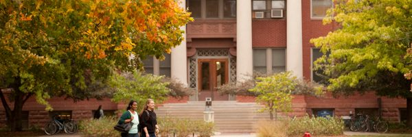 Two students stroll across campus in the fall