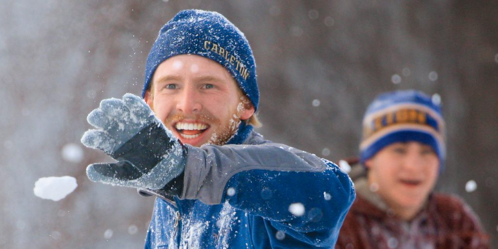A student in snow gear smiles as he holds up a hand to stop a friend's snowball from getting even more snow in his beard