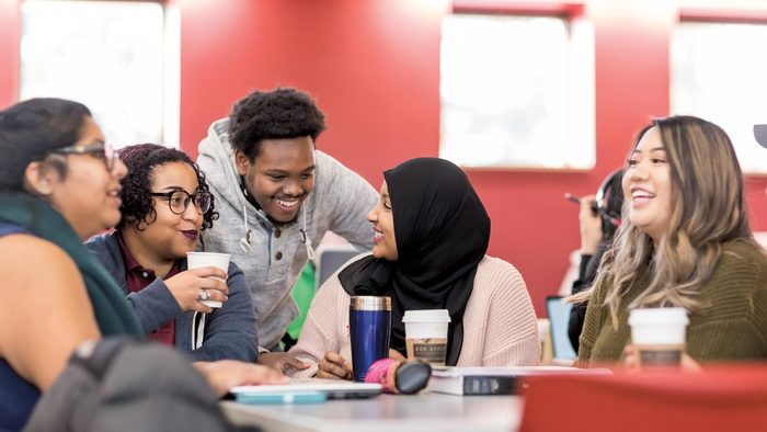 Three students — two women, one man — talking over coffee