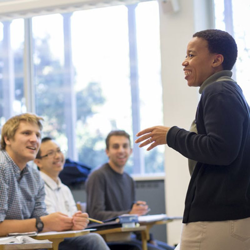 Students smile in class while a professor leads a lesson