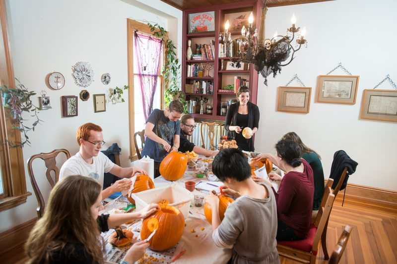 Professor Julia Strand carves pumpkins with her students.