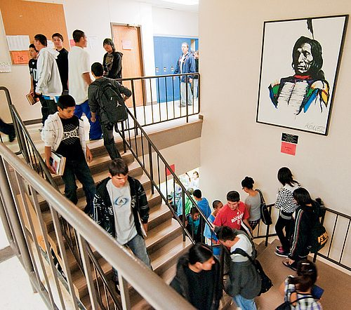 Students pass by a portrait of the school's namesake.