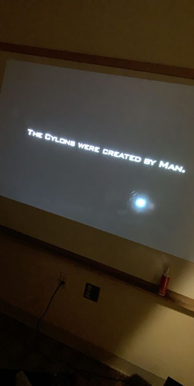 "Photo of opening scene of Battlestar Galactica projected onto a whiteboard, with a title card reading ""The Cylons were created by Man."""