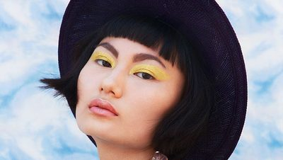 eve sporting yellow eyeshadow and a black hat