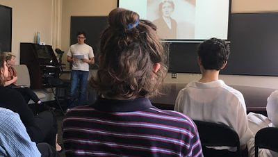 a classroom of students looking at a student presenting a slide of virginia woolf at the front of the room