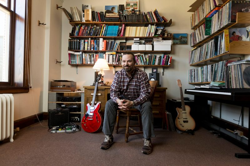 Professor Andy Flory in his office, surrounded by books, albums, and guitars