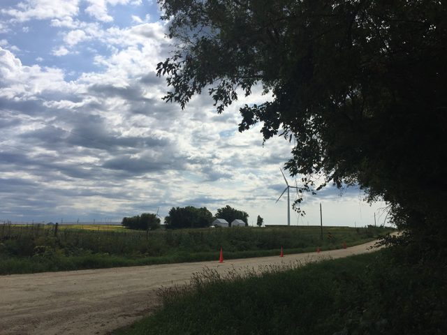 A gravel road with a wind turbine