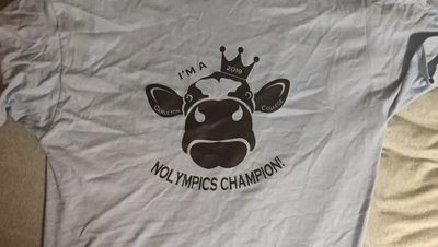 "a T-shirt with drawing of a cow and words ""I'M A 2019 CARLETON COLLEGE NOLYMPICS CHAMPION!"""