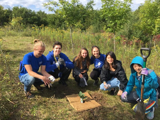 a group of students planting trees