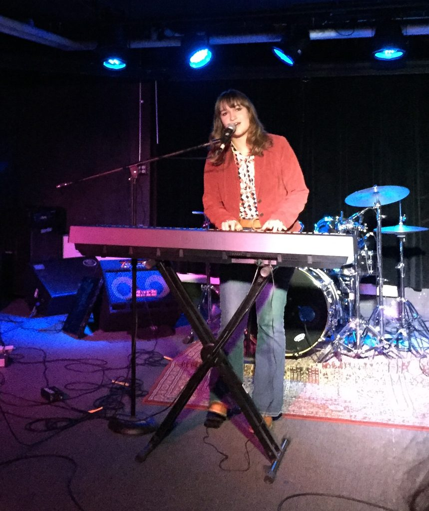 girl singing and playing piano