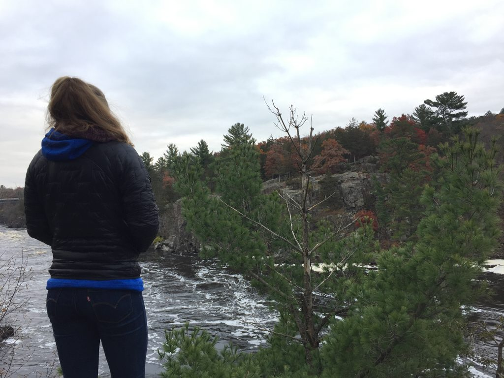 girl looking over river and rocks