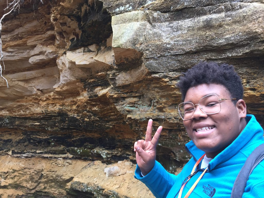 person with peace sign and rocks
