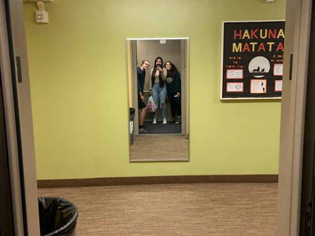 Three friends pose in mirror across from elevator.