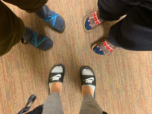 Three pairs of feet with socks and sandals.