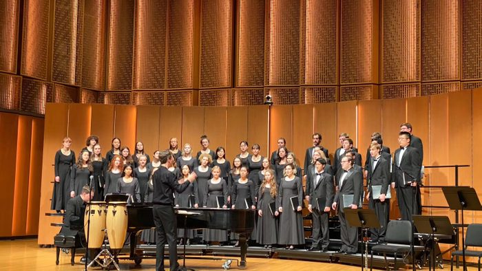 Indoor, students in Carleton Choir standing and performing on stage.
