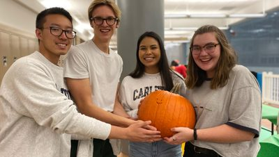 Four friends smile and hold a pumpkin