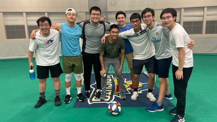 Picture of 8 male young adults in an indoor soccer field