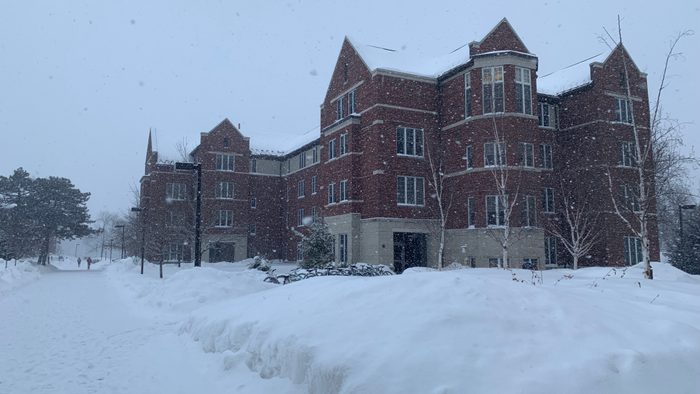 Cassat Hall from outside, covered in falling snow