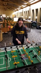 A Carl laughs while playing foosball in Sayles.