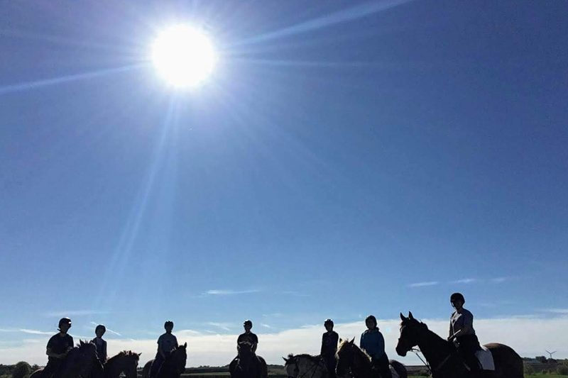 7 people are silhouetted on horseback