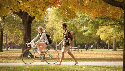 Two students walking by the Bald Spot in the fall