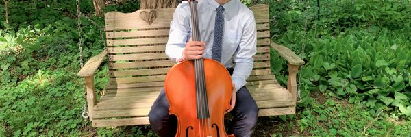 A picture of student Ewan Miller holding a cello