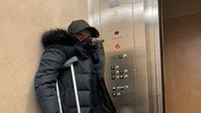 a person with crutches stands next to an elevator