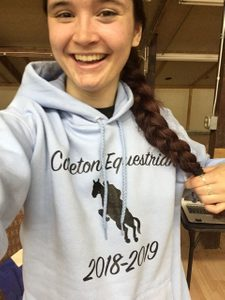 McKenna posing with her Carleton Equestrian hoodie