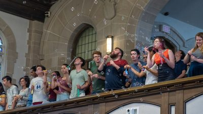 Students blowing bubbles down onto the professors during opening convocation