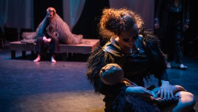 An actor cradling a doll in the Theater and Dance Department's production of That Wilderness of Glass