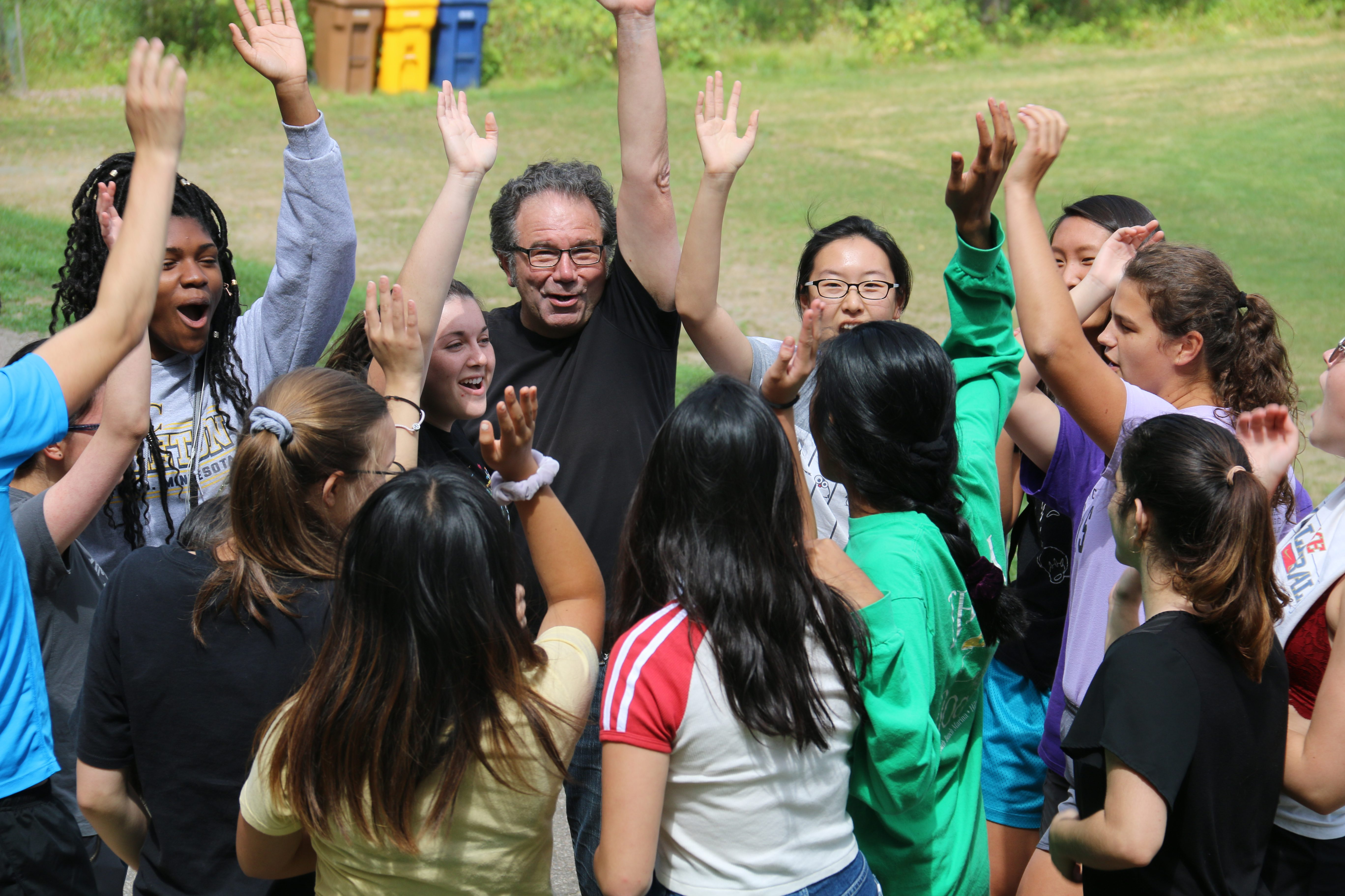 Students and teacher with their hands in the air